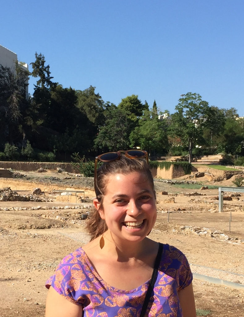 A white woman in a purple dress with sunglasses on her head smiles in front of an archeological site. The sky is blue and there are trees in the background.